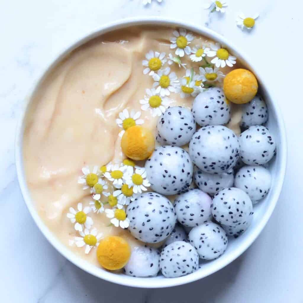 Citrus & Peach Smoothie Bowl  topped with dragon fruit balls and edible flowers