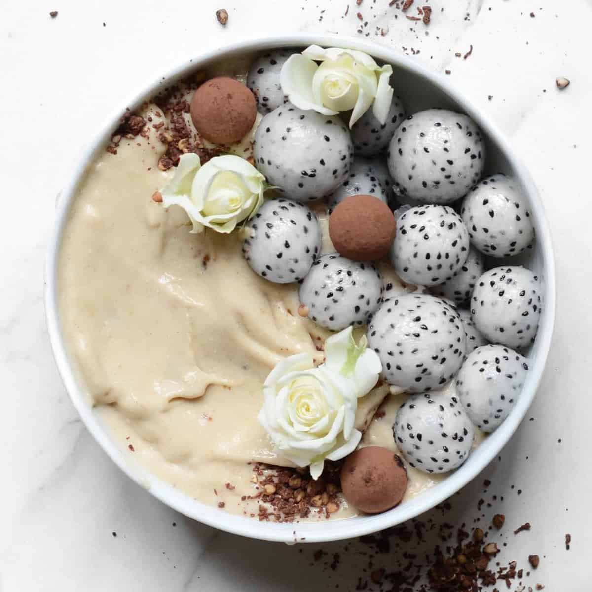 healthy salted caramel vegan smoothie bowl with dragonfruit and cacao protein balls. a delicious dessert smoothie