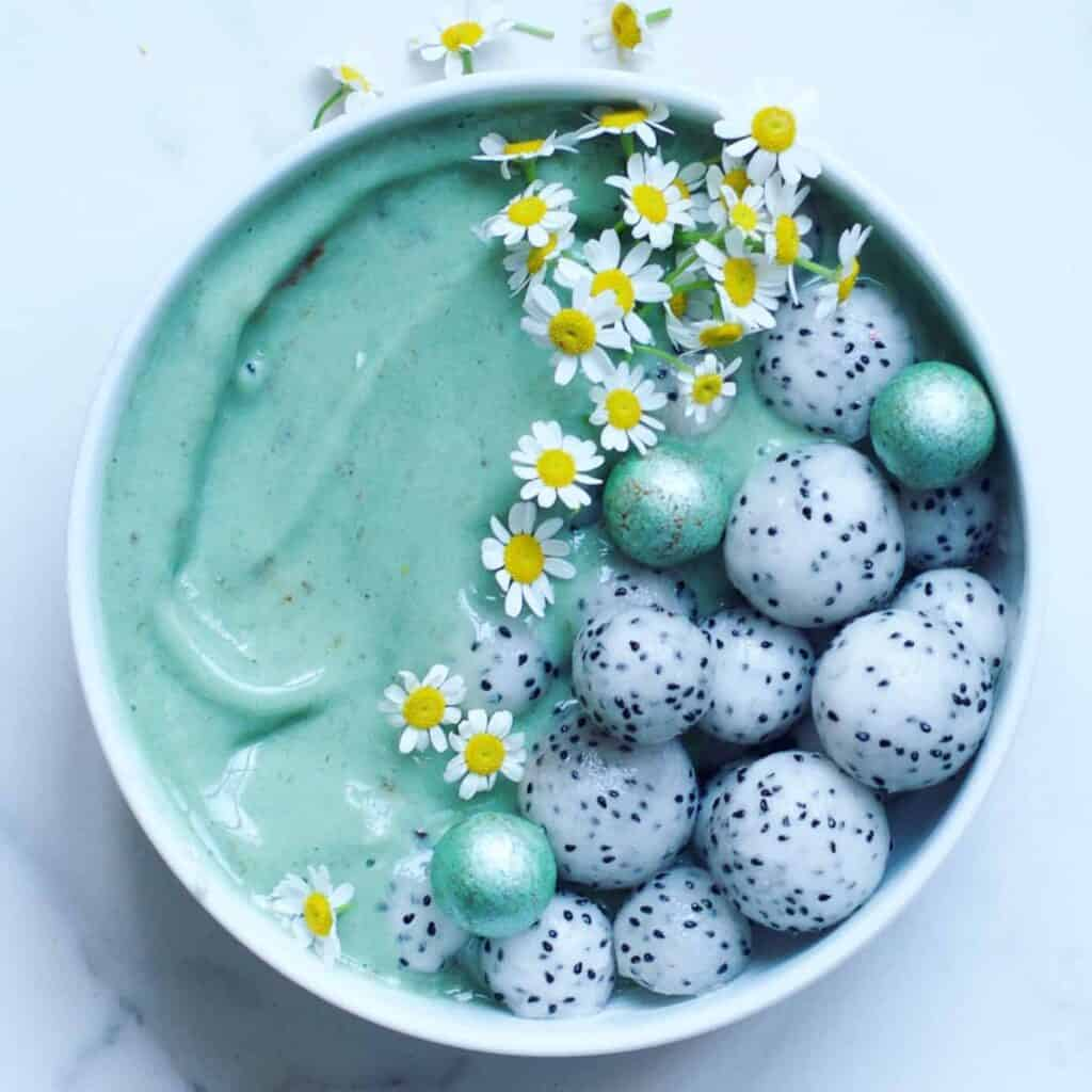 Spirulina Mint Choc Smoothie Bowl topped with edible flowers dragon fruit balls and blue chocolate balls