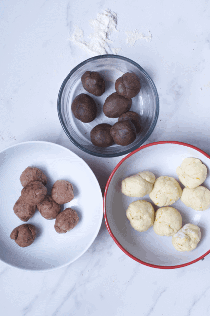 Different colored dough shaped in balls in three bowls