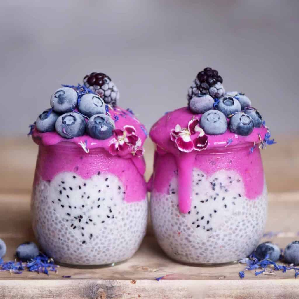 Pink Dragonfruit layered Chia Pudding jars topped with frozen blueberries