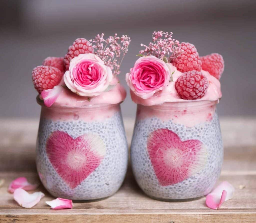 Strawberry and banana smoothie chia pudding jars decorated with frozen raspberries and edible roses. Delicious and nutritious vegan breakfast dish