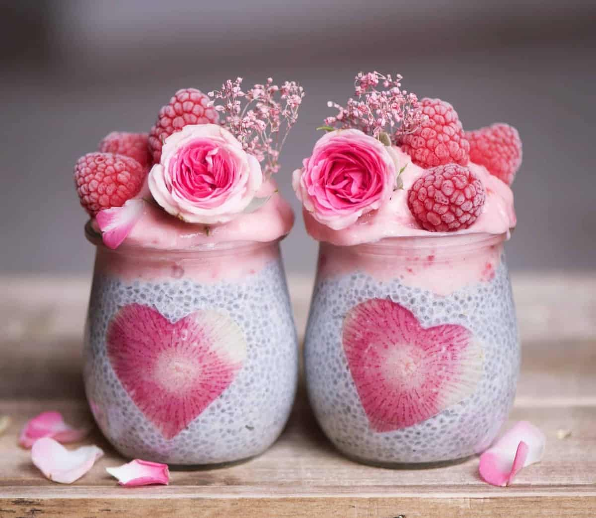 Strawberry and banana smoothie layered chia pudding jars decorated with frozen raspberries and edible roses. Delicious and nutritious vegan breakfast dish