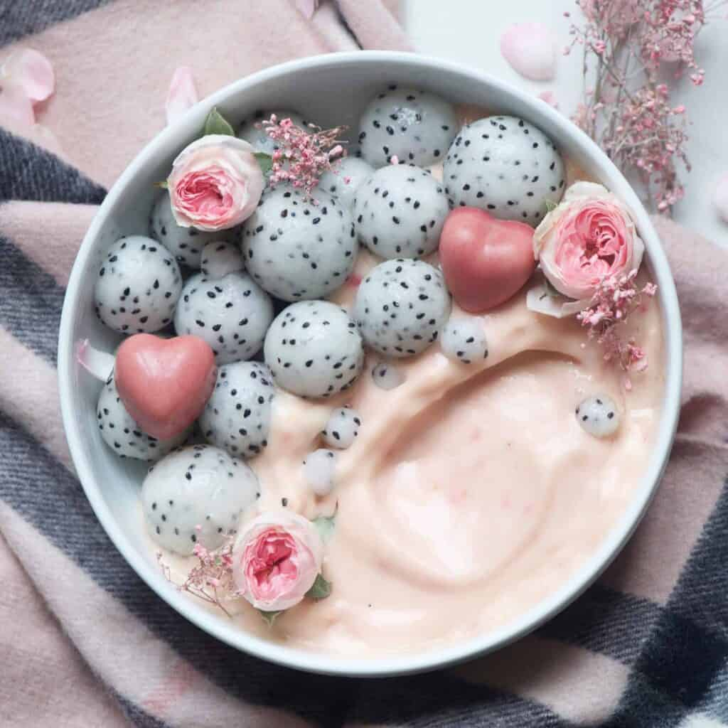 Raspberry and mango smoothie in a bowl topped with dragonfruit balls and heart shaped chocolates and edible roses