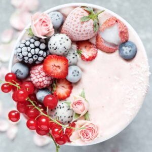 A no banana smoothie bowl decorated with frosted red berries and edible flowers