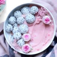 A bowl of pink smoothie with dragon fruit balls and edible flowers