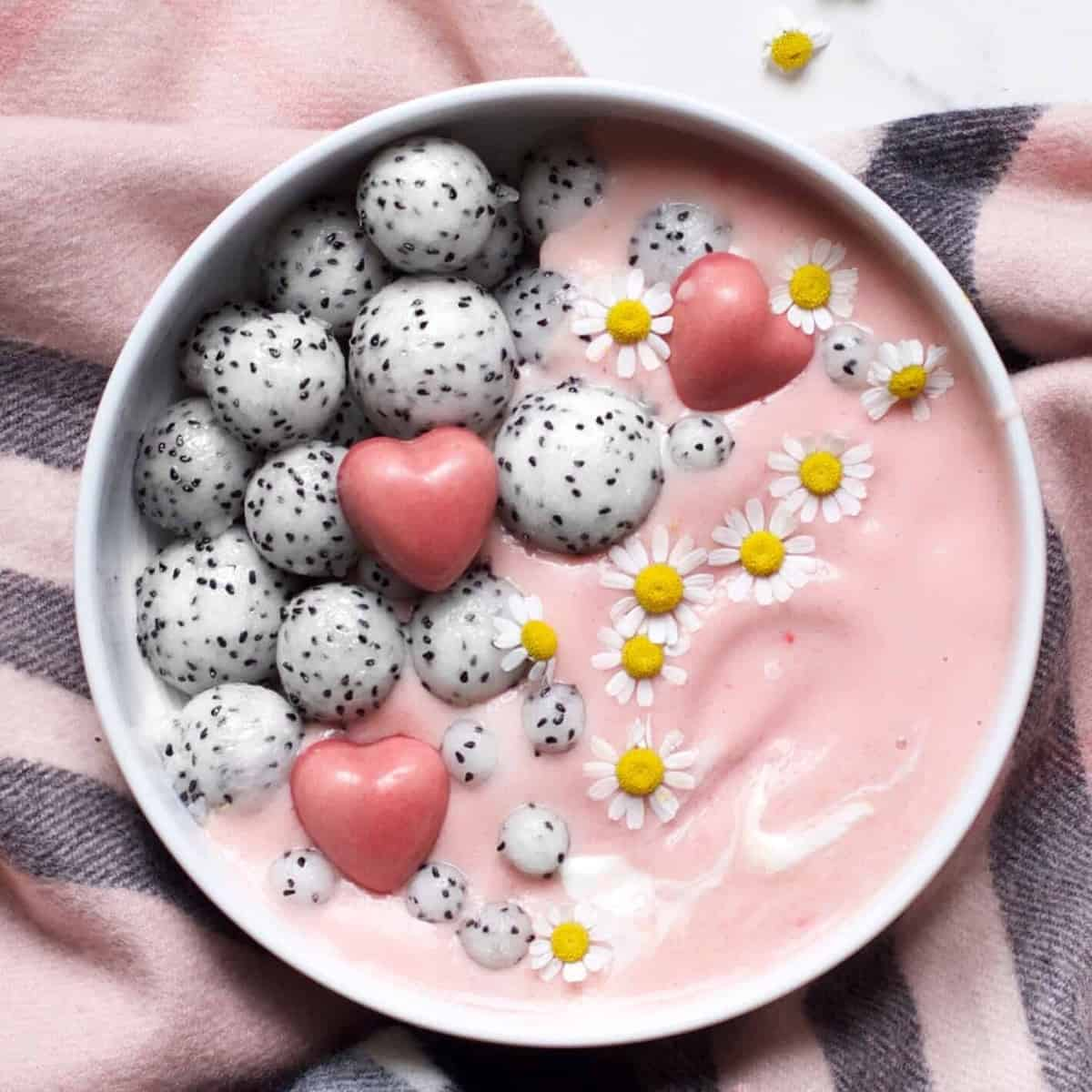 A bowl with pink smoothie and some dragon fruit balls pink chocolate hearts and edible camomile flowers