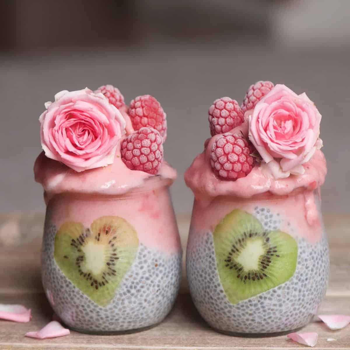 Two jars with chia pudding pink yogurt decorated with frosted raspberries and edible roses