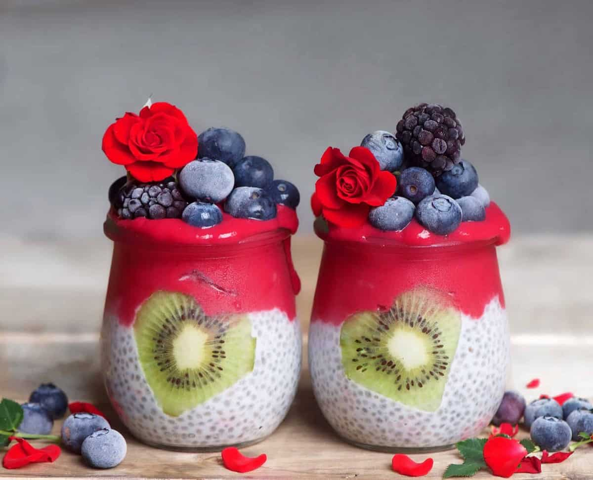 Two jars with chia pudding with red yogurt decorated with blueberries and edible roses