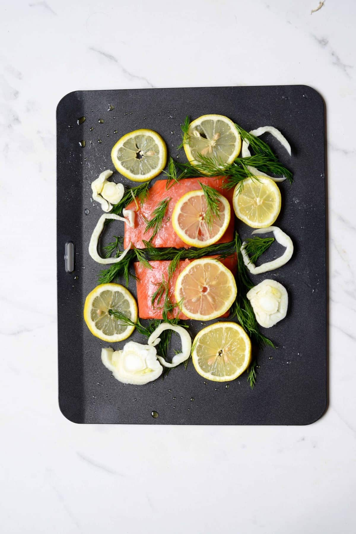 Salmon and lemon slices on a baking tray