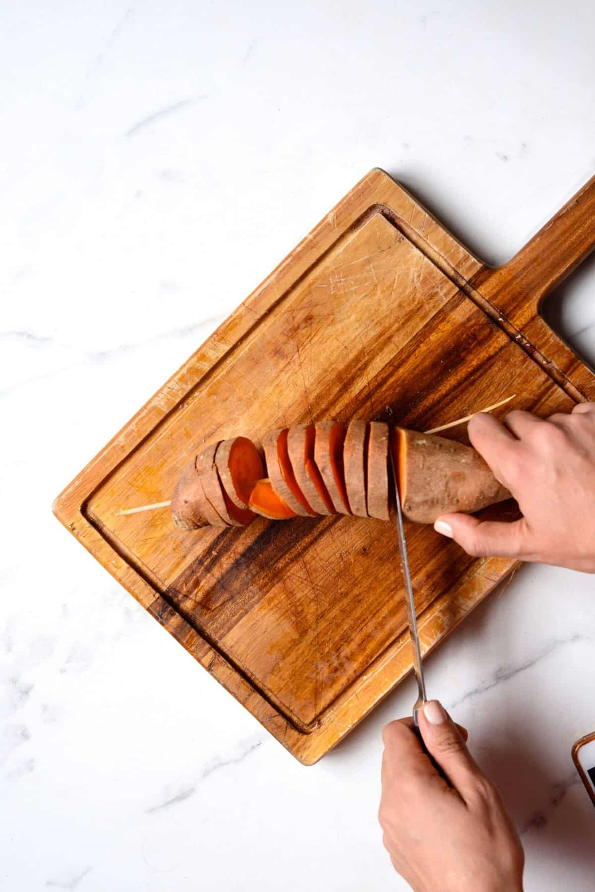 Slicing a sweet potato on a skewer