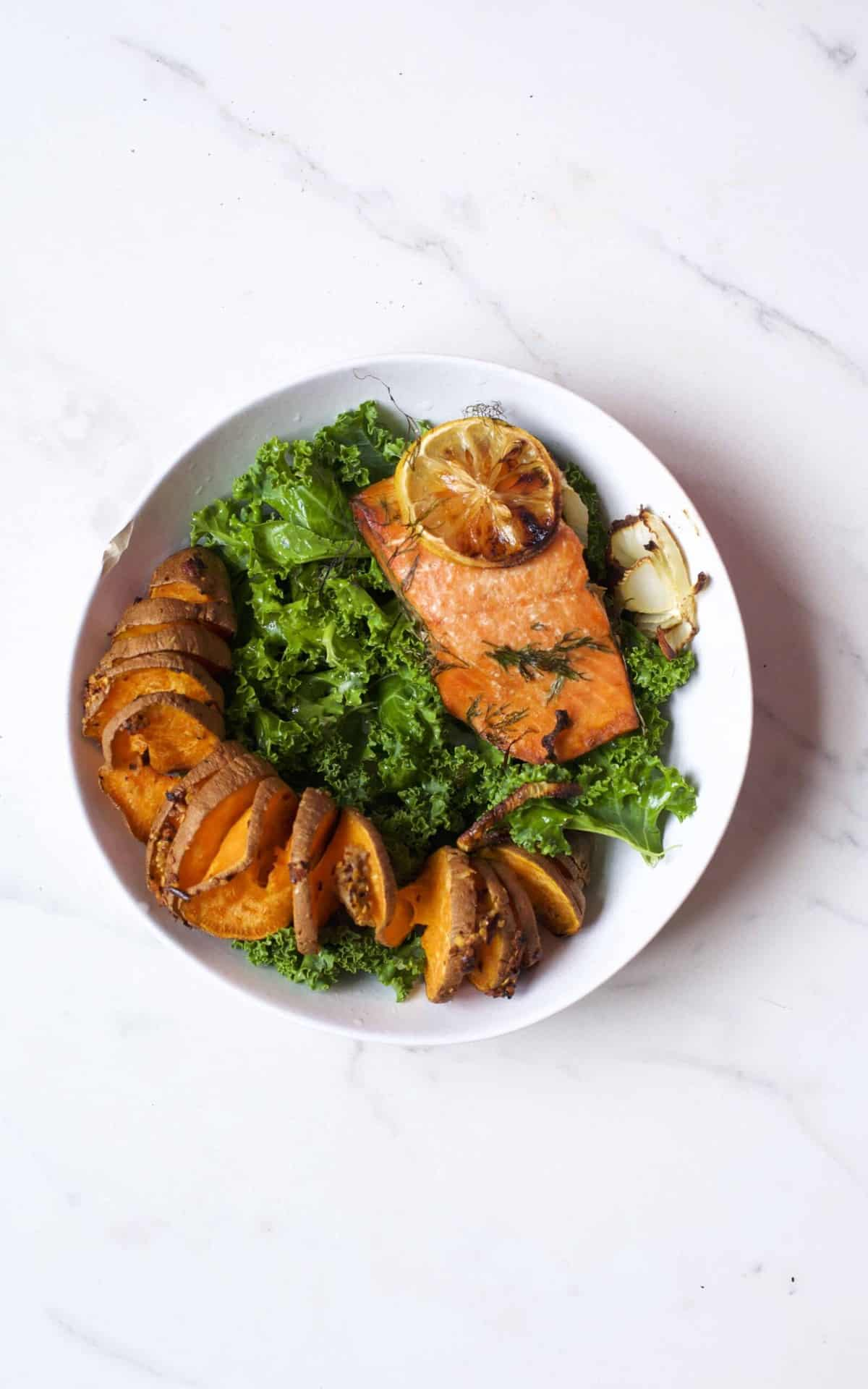 Grilled salmon with cake and baked sweet potato in a bowl