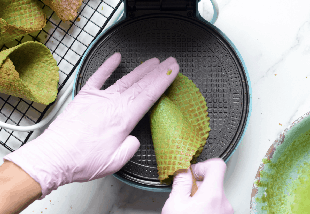 Making a waffle cone with a freshly baked waffle in a waffle machine