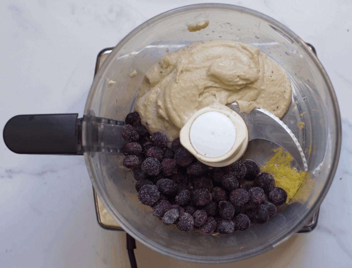 Blending blueberries with cashews in a blender