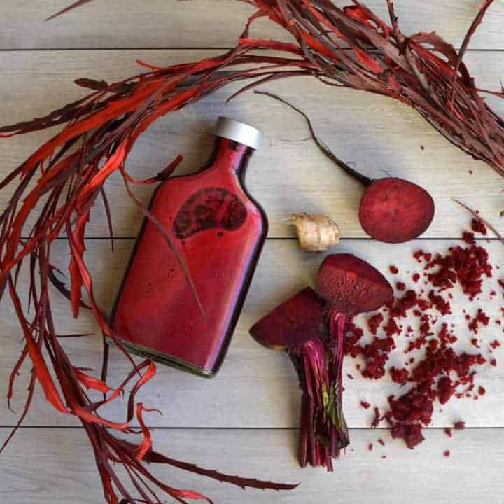 Beetroot and ginger juice in a bottle and a few pieces of beetroot and a ginger slice on a wooden background