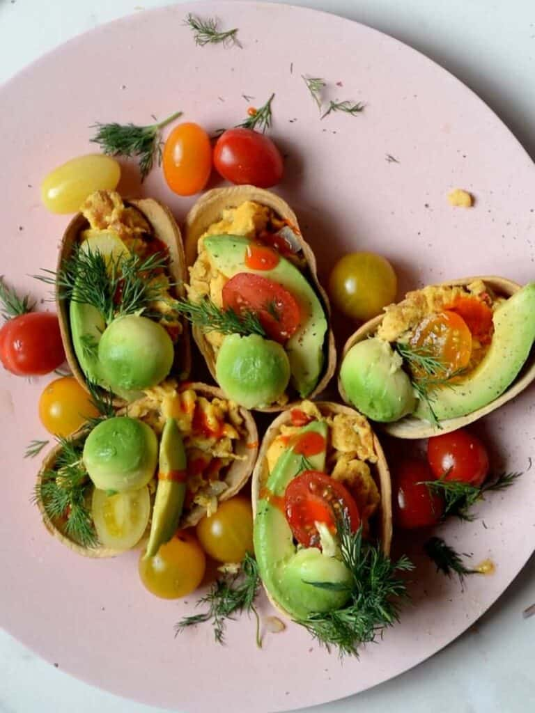 Ingredients for breakfast tacos server with avocado and tomatoes