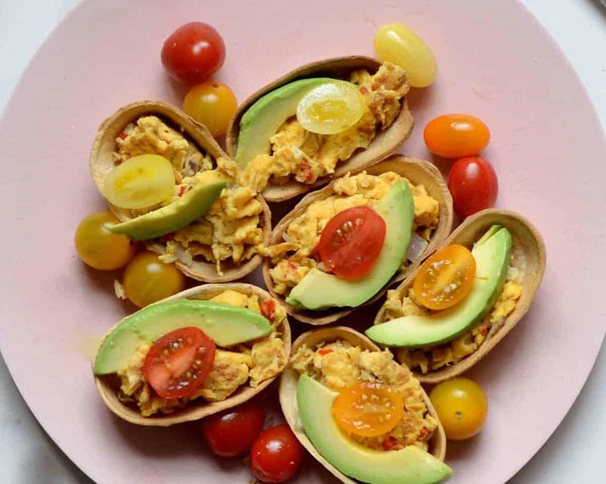 Breakfast tacos topped with avocado and cherry tomatoes