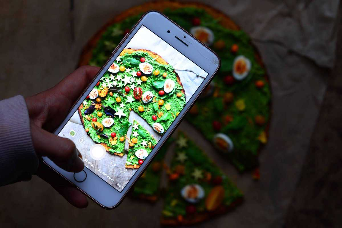 Butternut Squash base pizza with green sauce seen on a phone screen