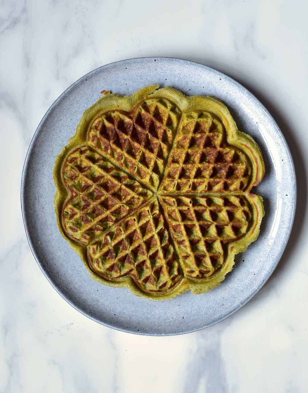A green matcha waffle served in a plate