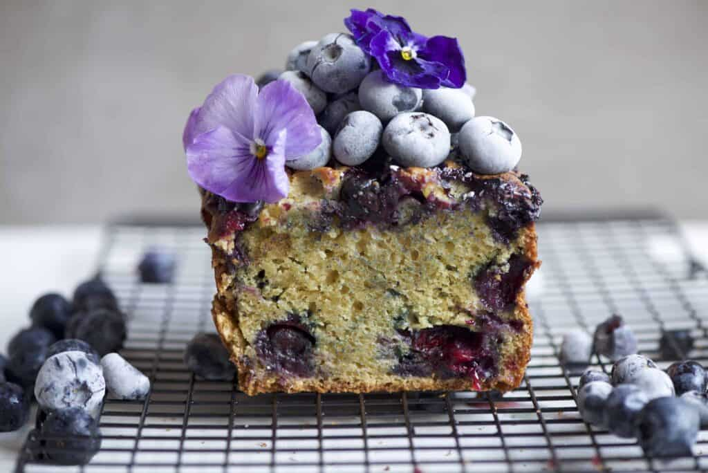 lemon blueberry loaf cake topped with frozen blueberries