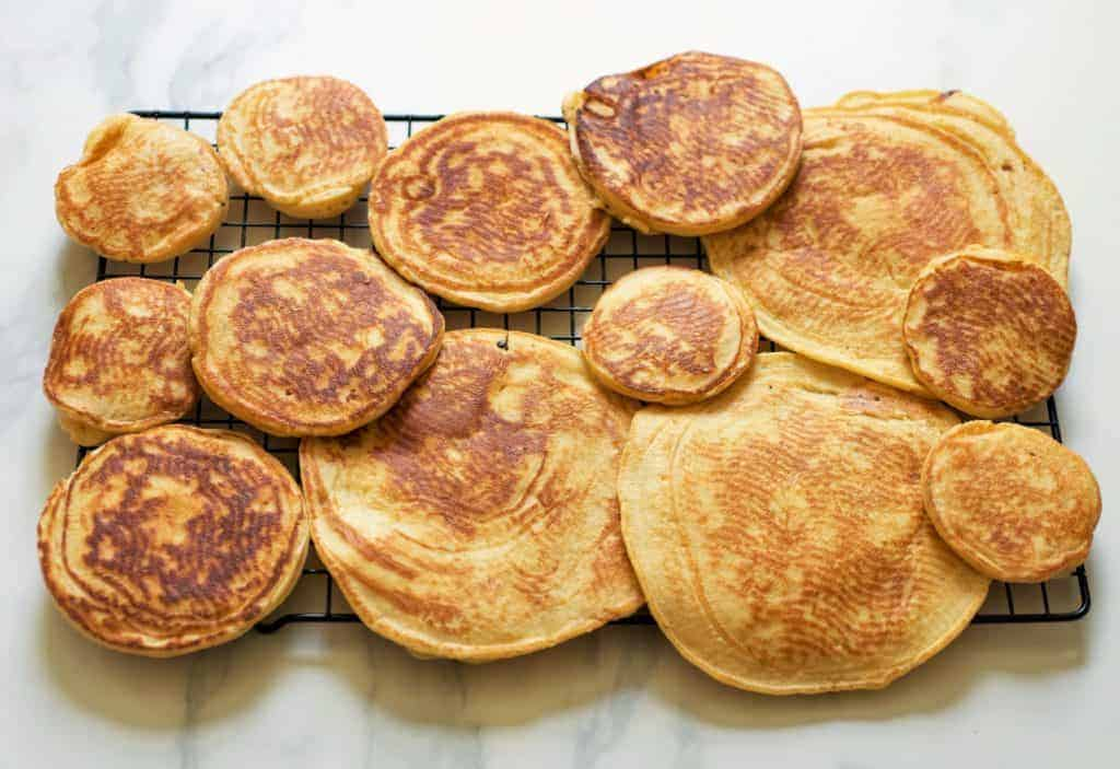 pancakes different sized on a cooling rack