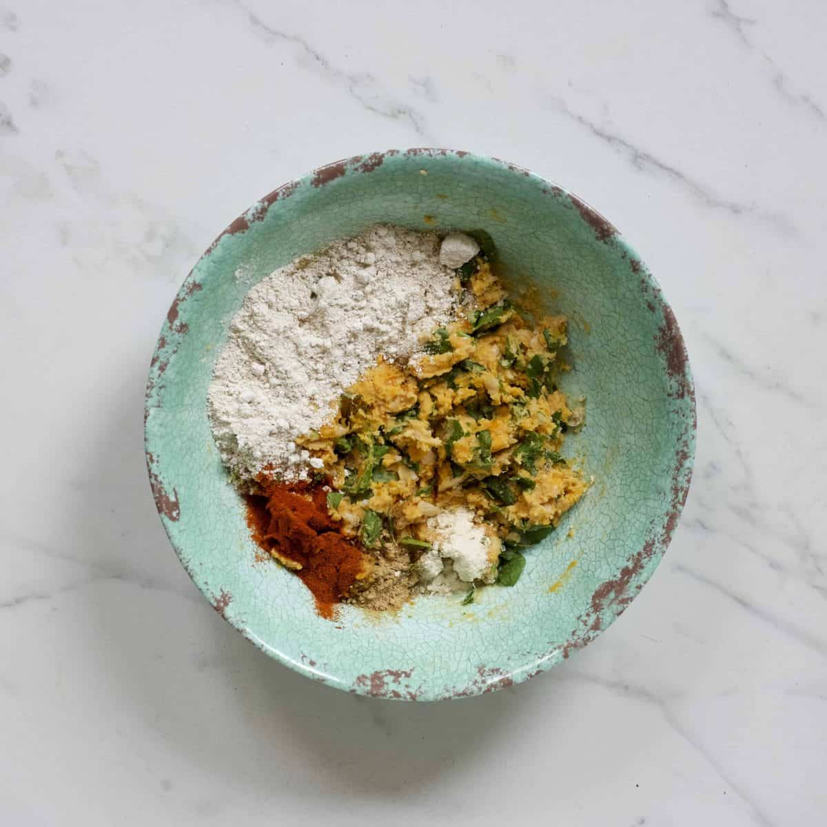Mixing sweet potato with spices and flour