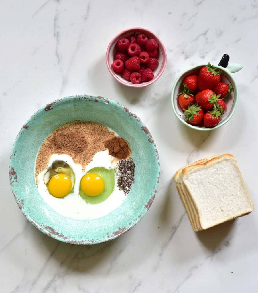 eggs, milk, cinnamon, vanilla in a bowl next to bread and berries