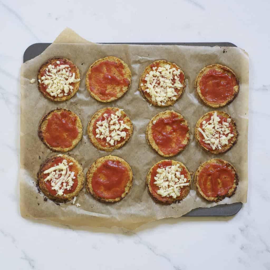 topping mini pizzas with marinara sauce