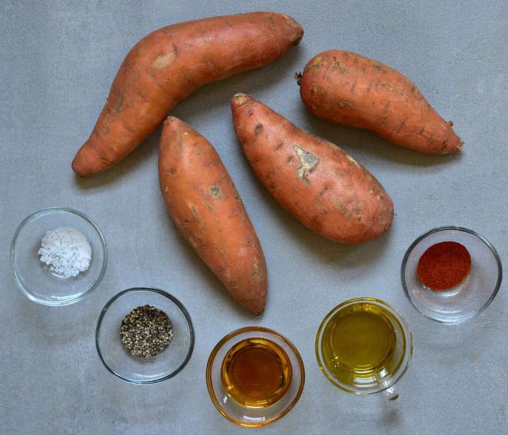 Four sweet potatoes and small bowls with spices