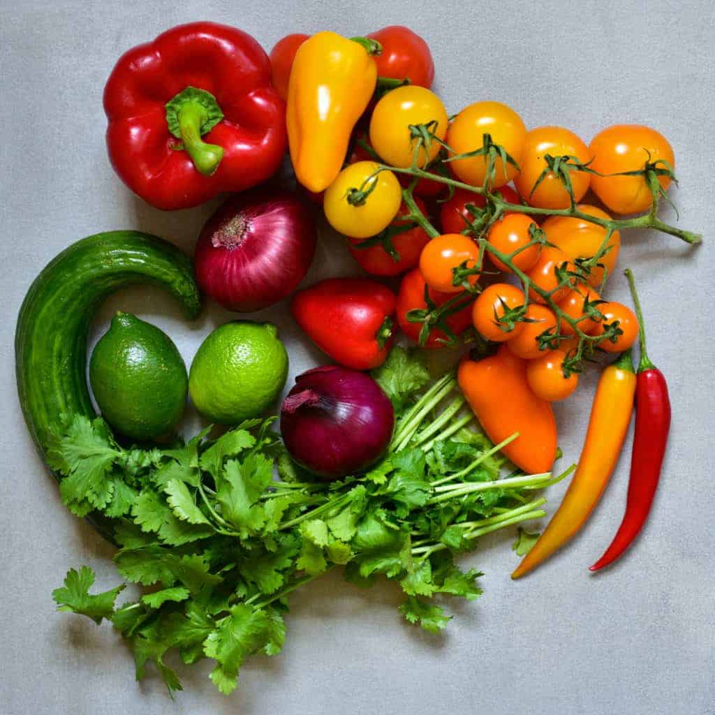 Colorful vegetables including peppers cherry tomatoes onion cucumber lime and parsley