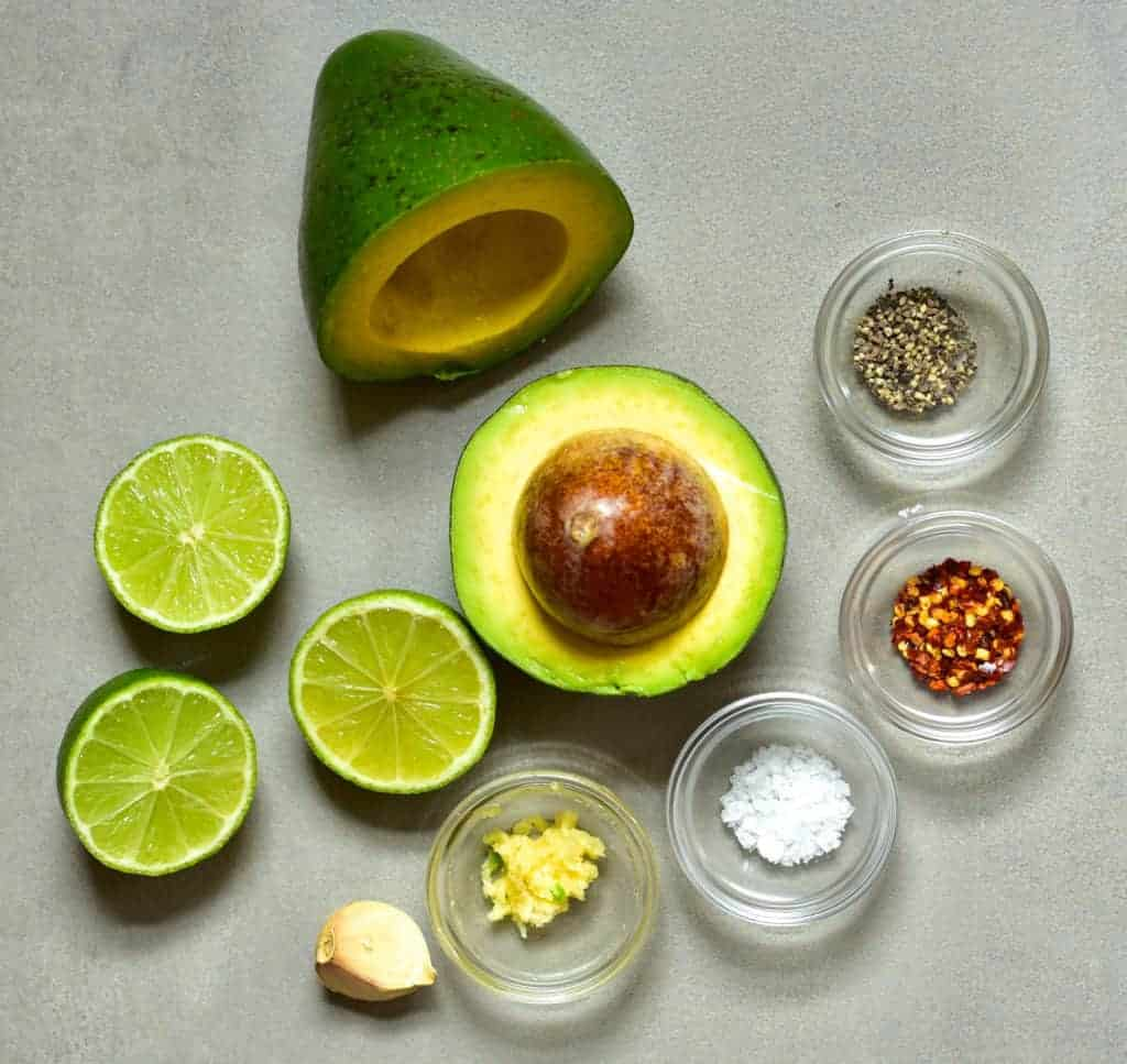 Avocado cut in half with lime and spices next to it
