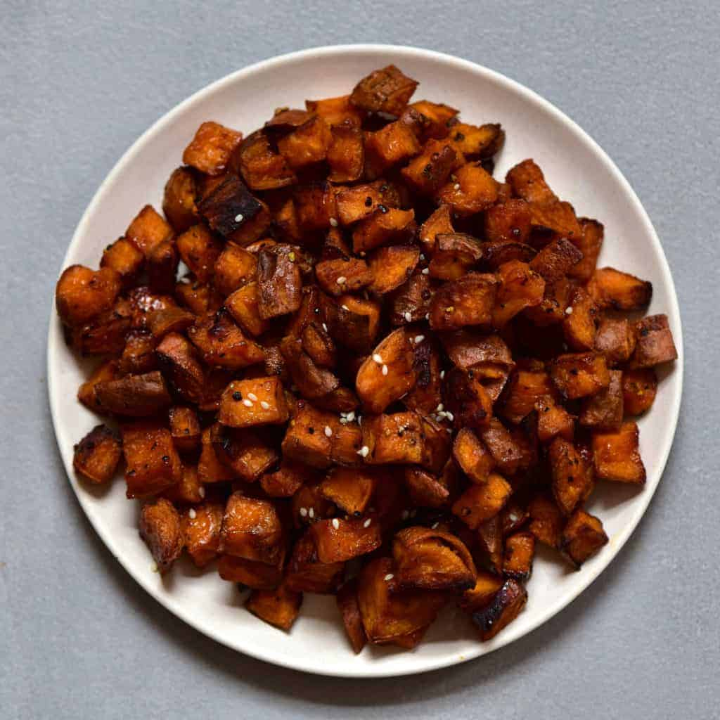 Baked sweet potato cubes on a white plate