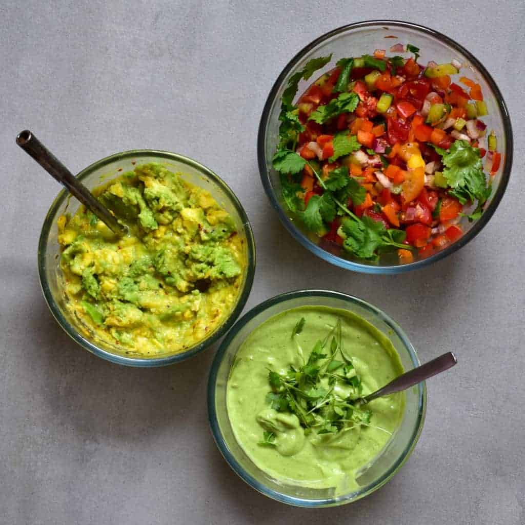 A bowl with pepper salsa, a bowl with guacamole and a bowl with green dipping sauce