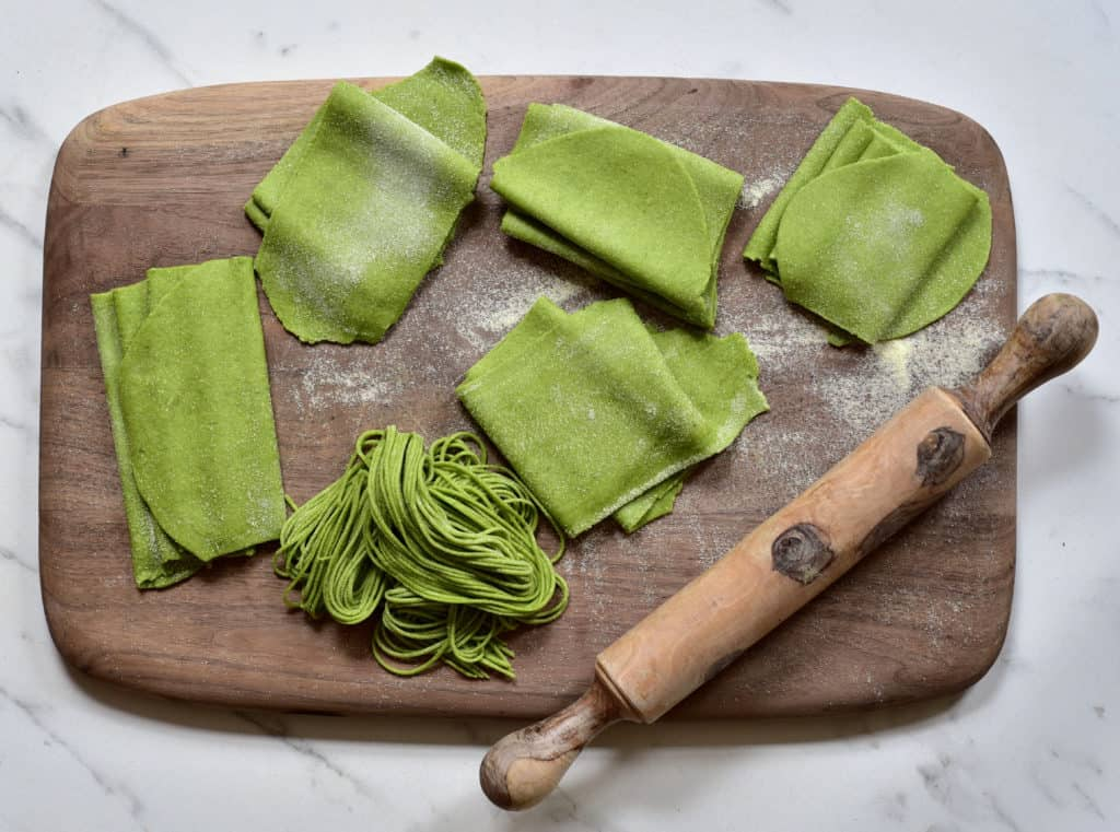 Fresh green home-made green pasta salad with spinach, green pistachio basil pesto and Kale