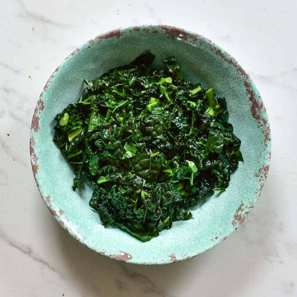 massaged kale in large bowl with dressing