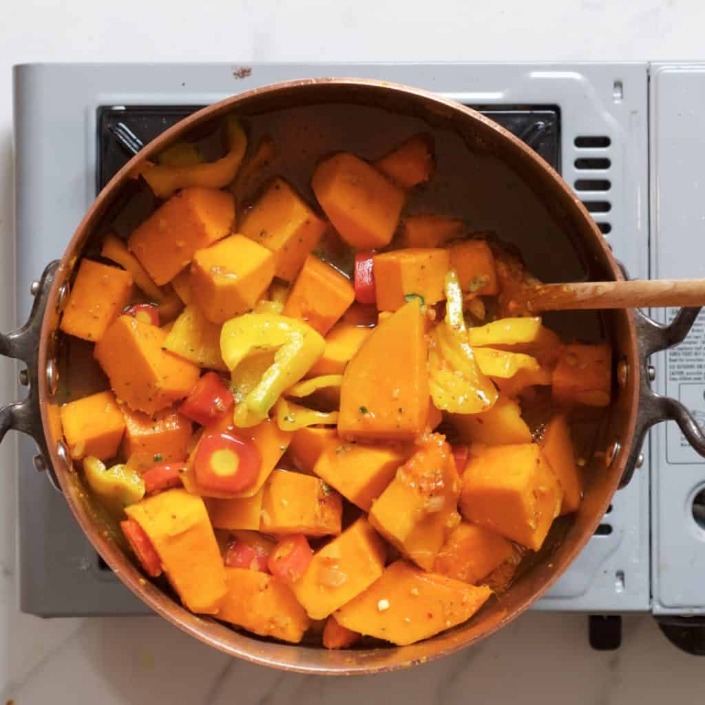 Pumpkin carrots and peppers cooking in a pot