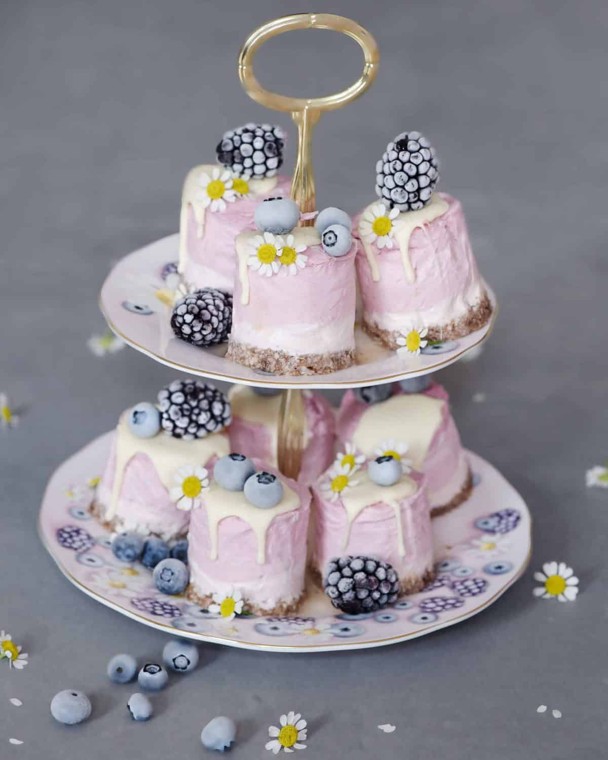 Individual portions of pink cheesecake served with frosted berries on a two-tier plate