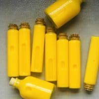 Nine small glass vials filled with turmeric and lemon shots laying on a flat gray surface