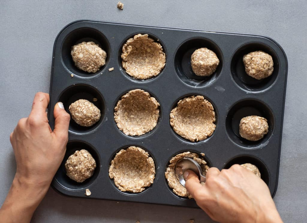 shaping granola cups in baking tray