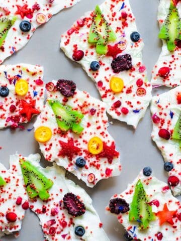 Yogurt bark pieces decorated with red puffed quinoa kiwis and other fruit