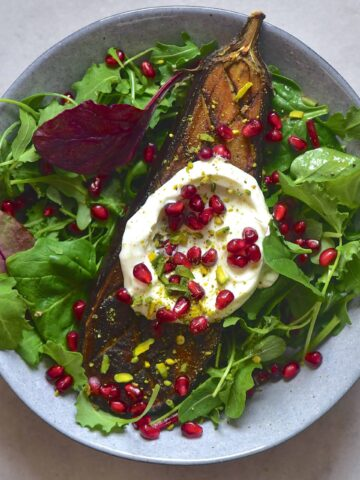 Half a roasted aubergine with green salad leaves yogurt and pomegranate seeds