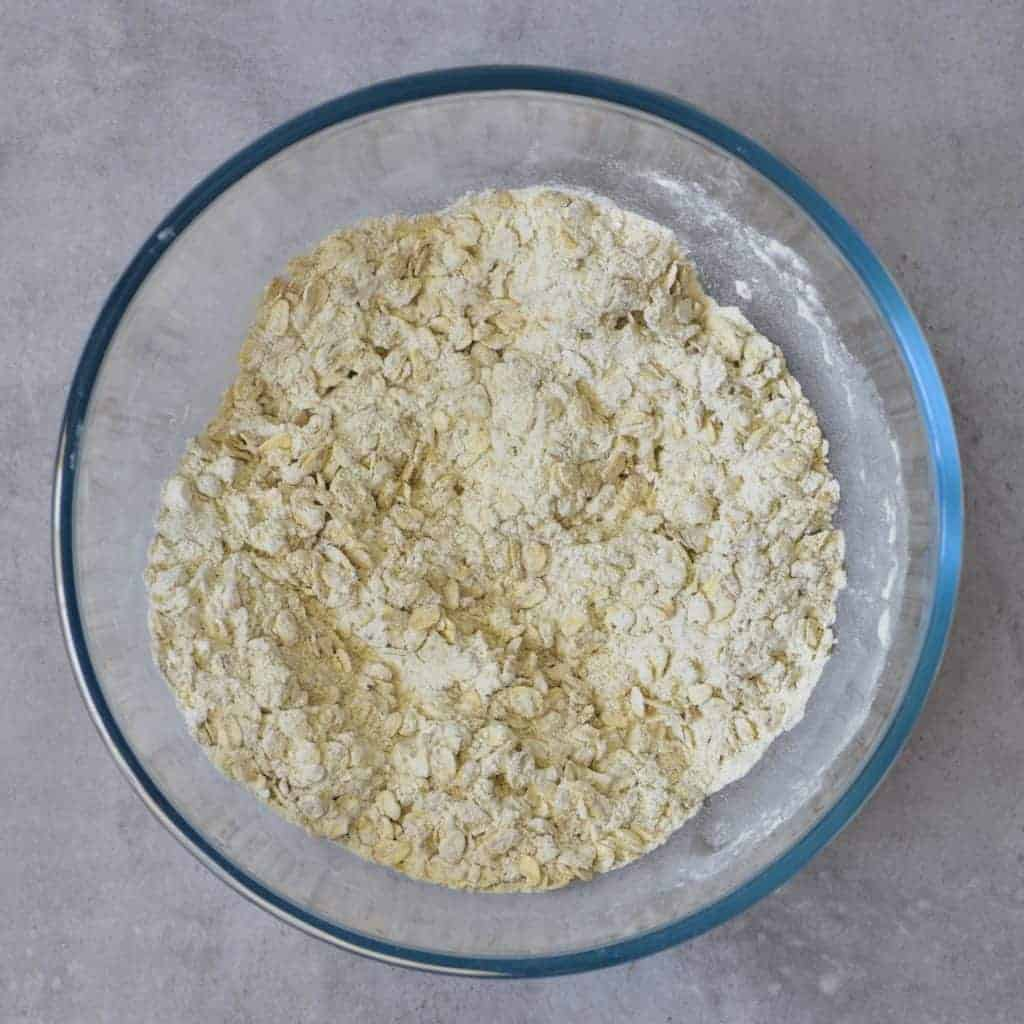Mixing flour and oats in a bowl