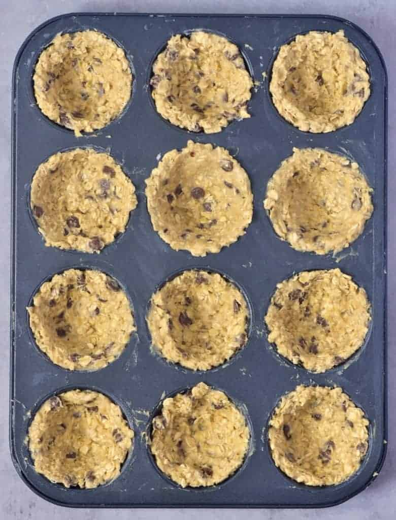 Cookie batter divided into muffin tin