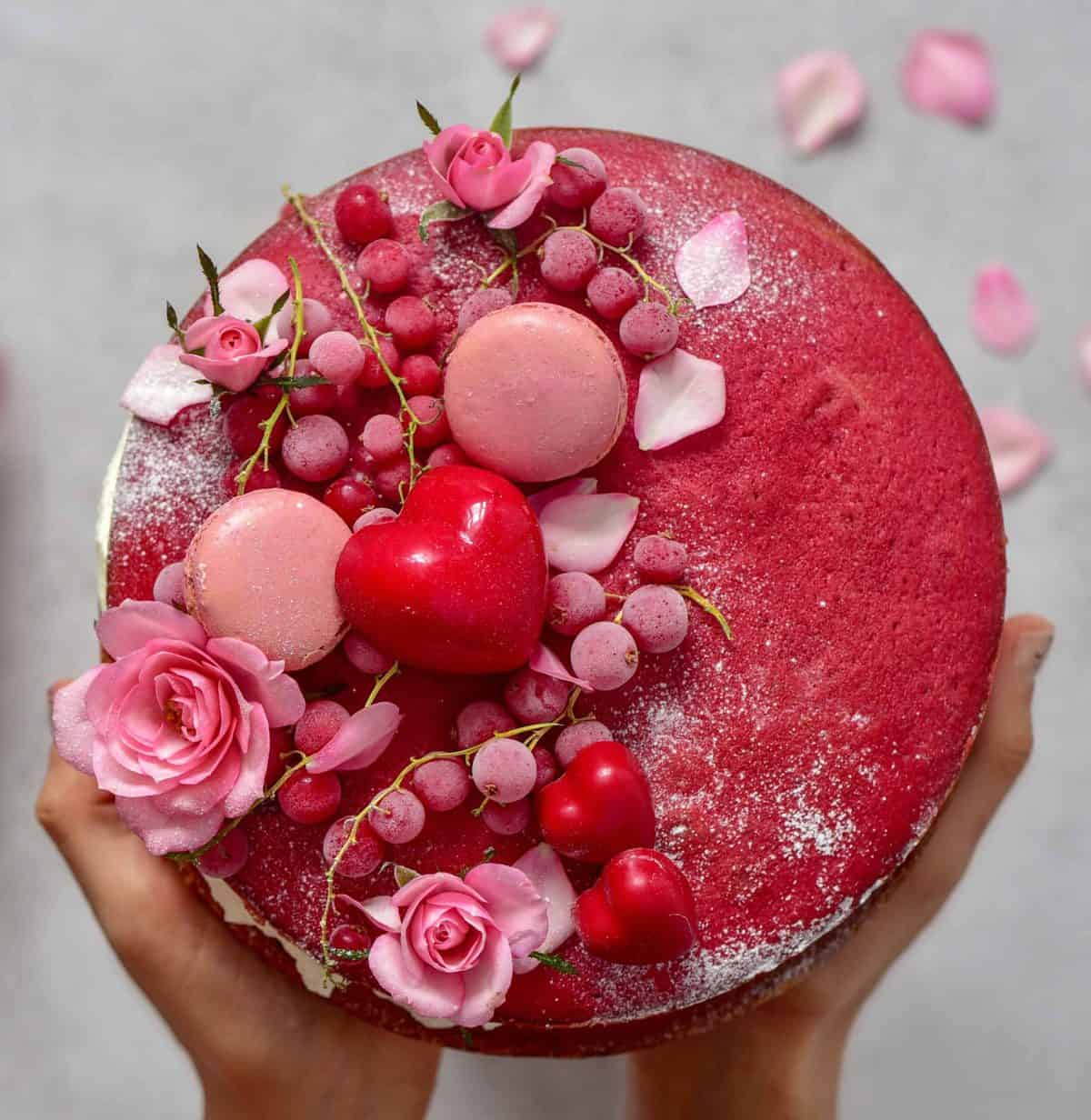 homemade red velvet cake topped with berries, chocolate heart bonbons, and edible flowers