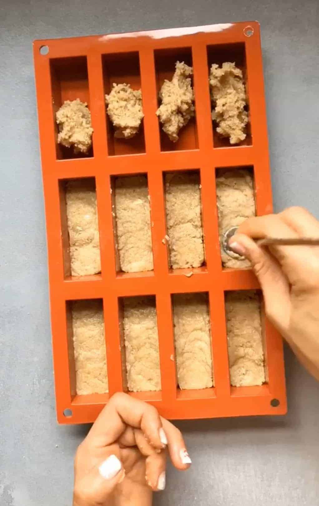 pressing nougat layer into silicone mold for homemade snickers bars