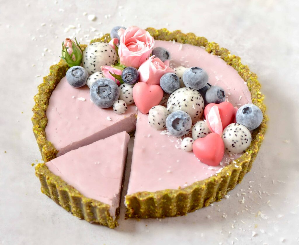 Vegan Pistachio, Strawberry & Rose Tart topped with blueberries, dragon fruit and edible roses