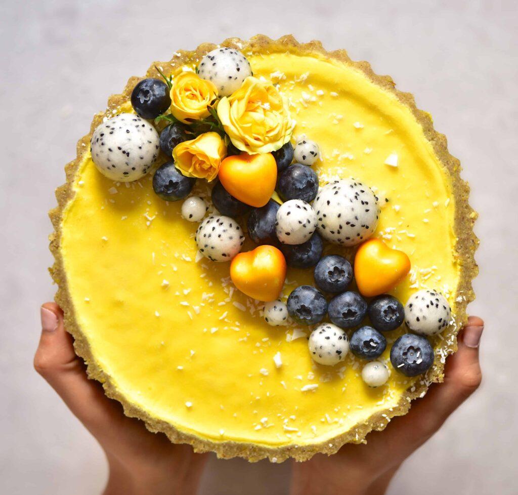 vegan pistachio & lemon tart topped with dragon fruit, roses and blueberries