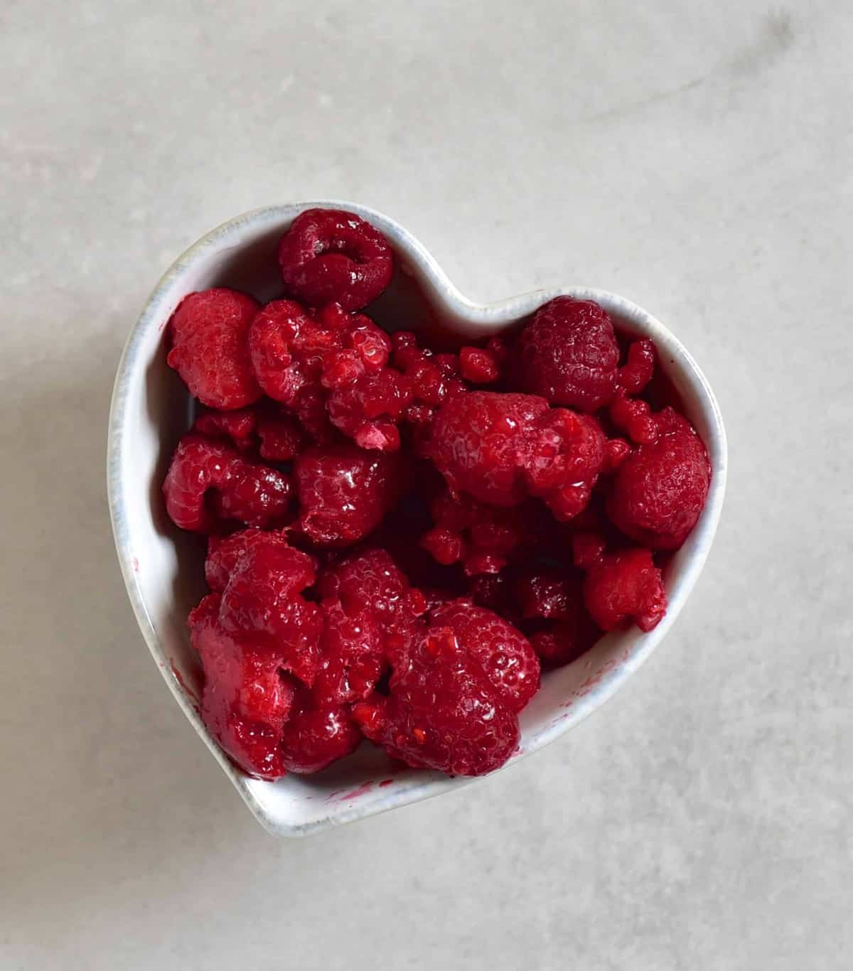 raspberries thawing in small heart-shaped bowl