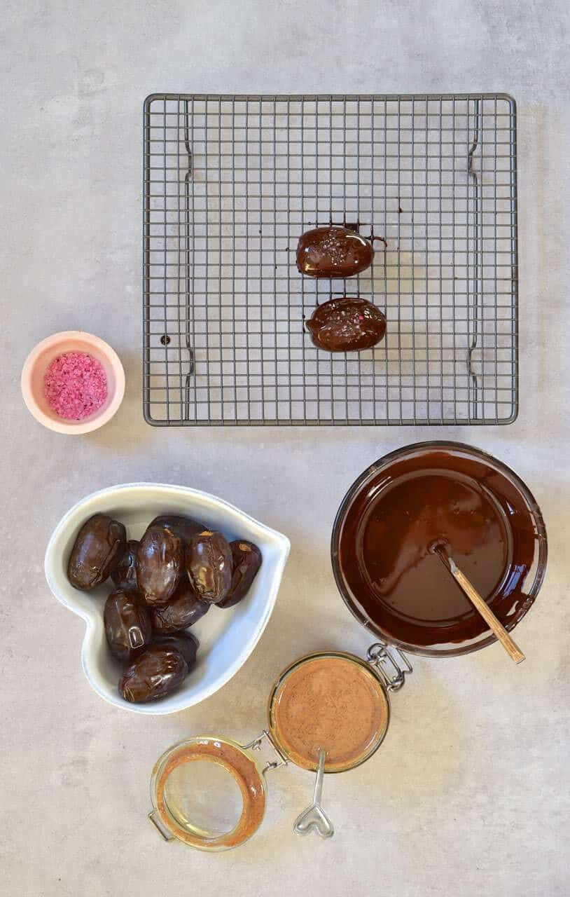 assembly ingredients for stuffed dates melted chocolate, almond butter and pink salt