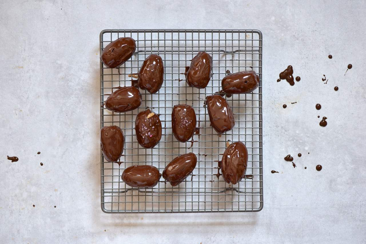 chocolate covered dates on a cooling rack for the chocolate to set